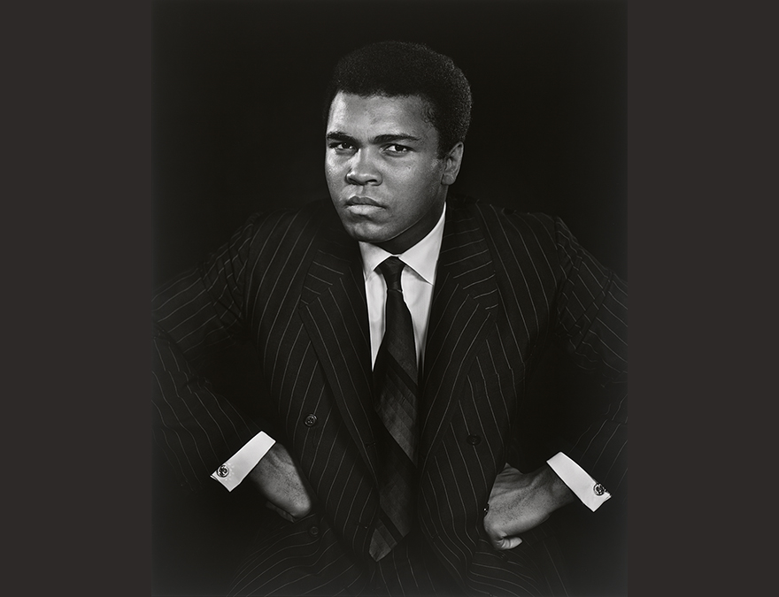 Black and white photograph of Muhammad Ali in a dark suit.