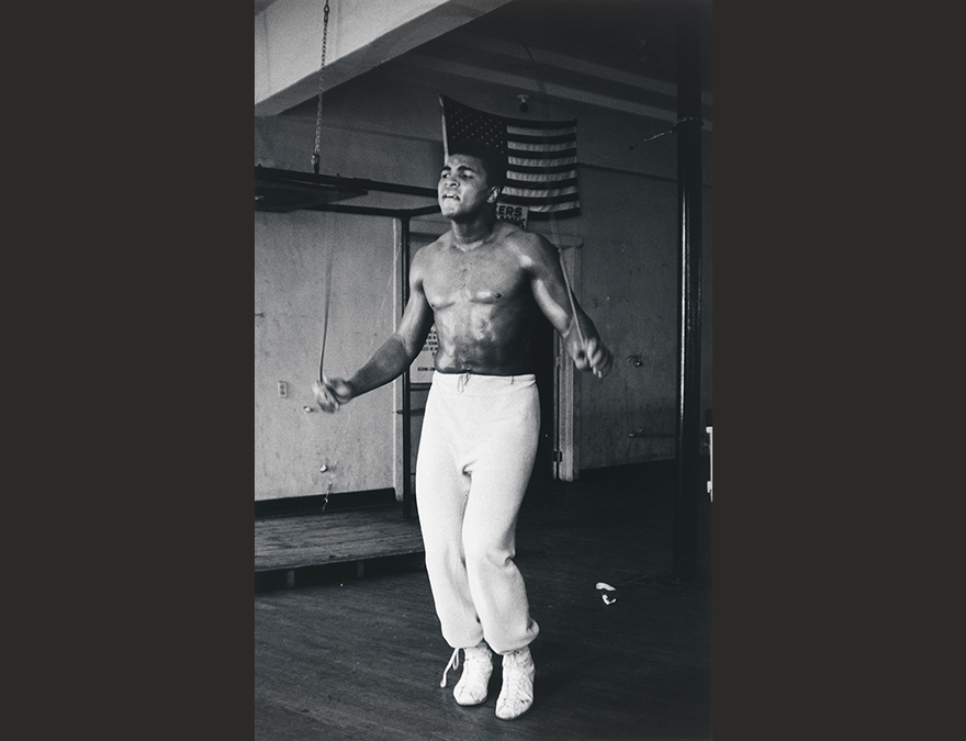 Bare-chested man in white warm-ups jumping rope.