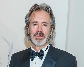 bearded man with gray hair in a tuxedo
