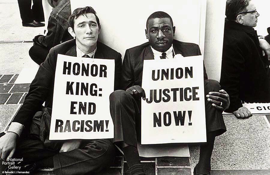 A black and white photograph of two men holding protest signs