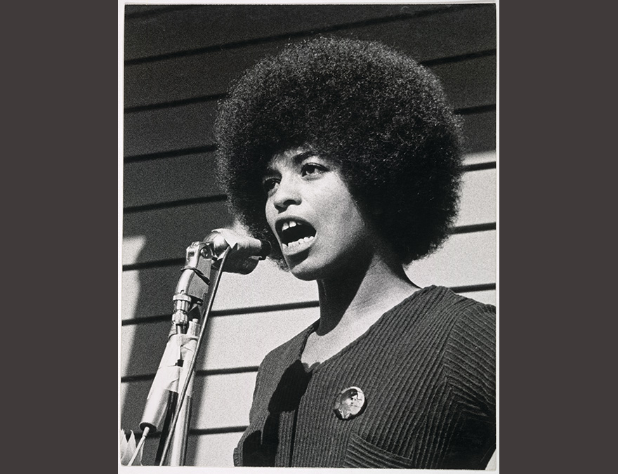 Young African American woman speaking at a microphone