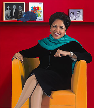 woman in a black dress seated against a red background
