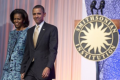 Barack and Michelle Obama, in formal attire, next to podium with Smithsonian logo