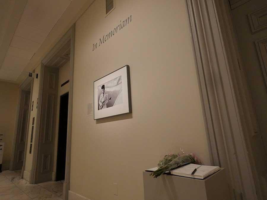 The Prince portrait display showing memory book and flowers that museum visitors have left