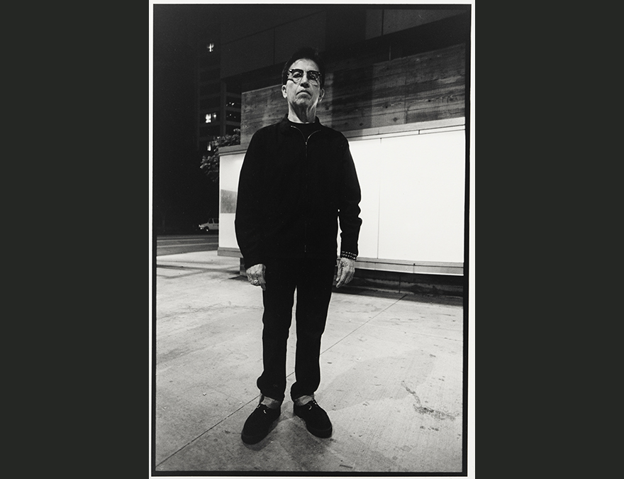 Full length photo of a man dressed in black