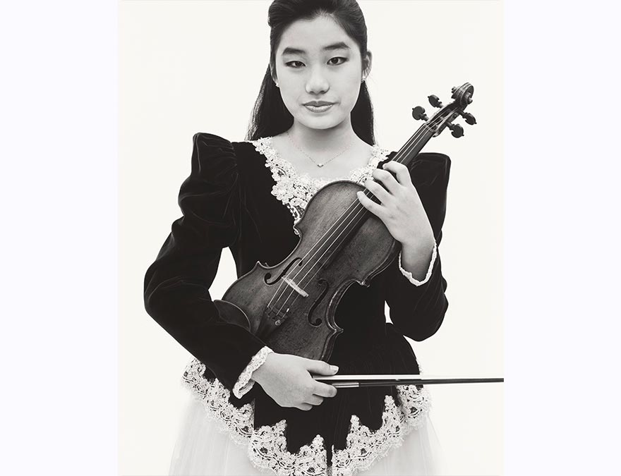 young Asian woman with long hair and formal dress holding a violin