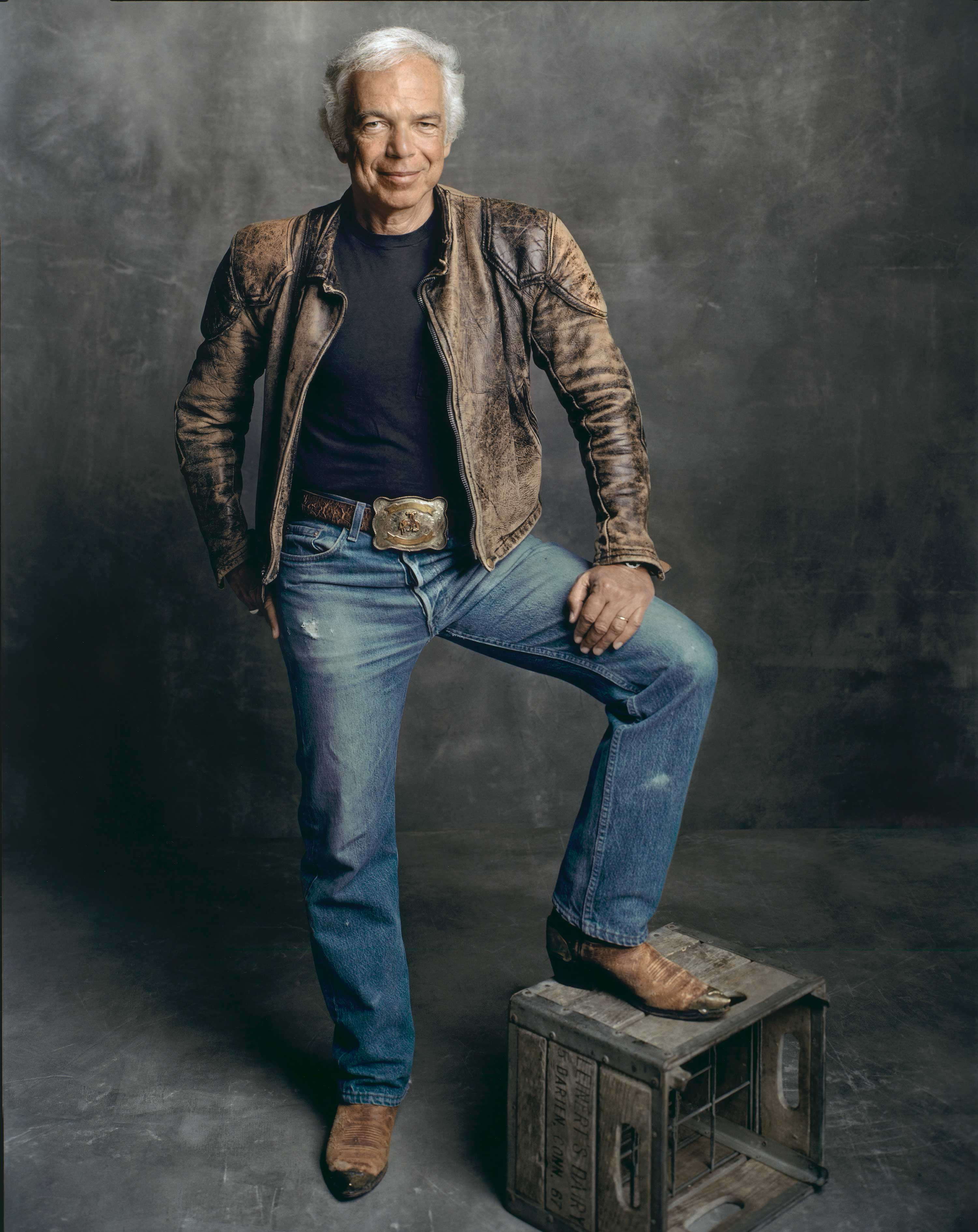 Photograph of a man standing on a wooden crate and wearing a leather jacket