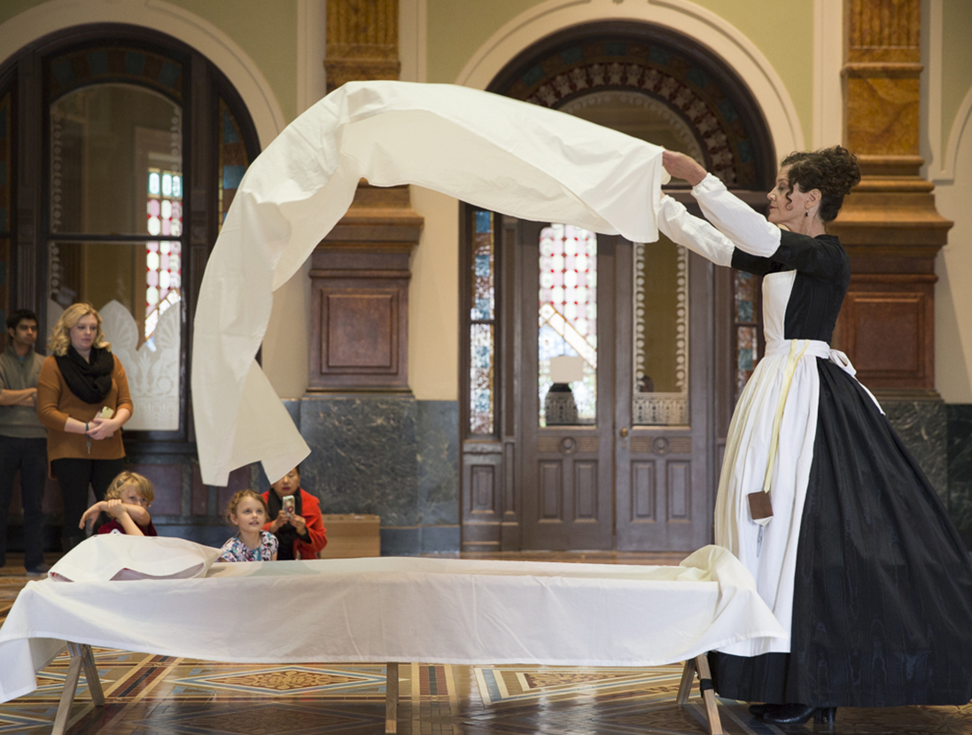 Woman throwing a sheet over a cot