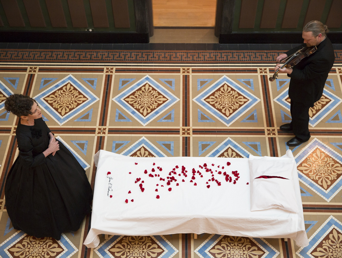 View from above of one of the cots covered in s white sheet and covered in rose petals