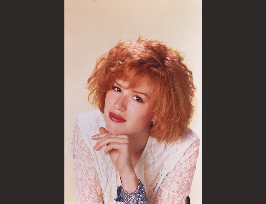 YOung woman with red hair with her hand under her chin