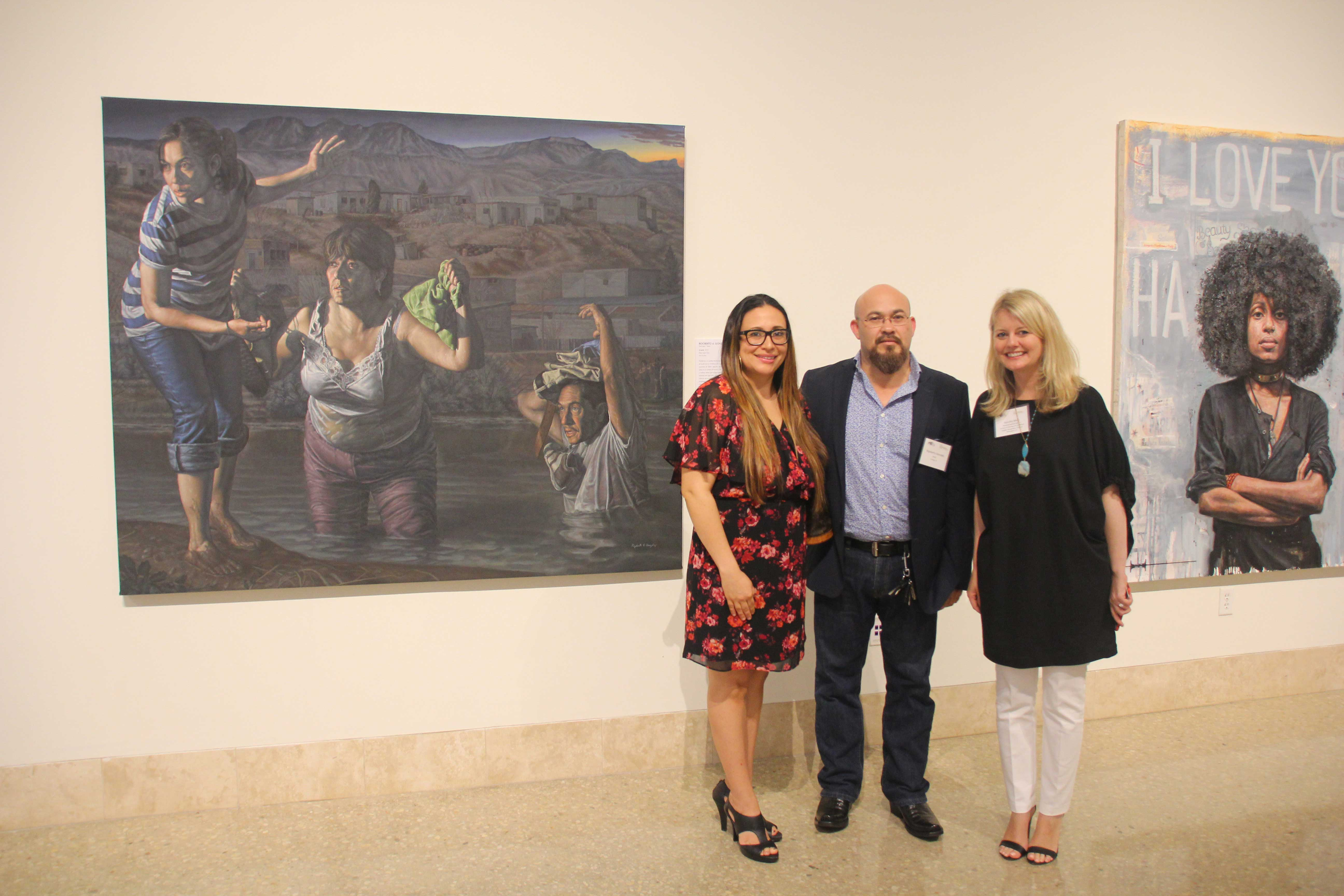 Three people standing in front of a painting of people escaping form a river