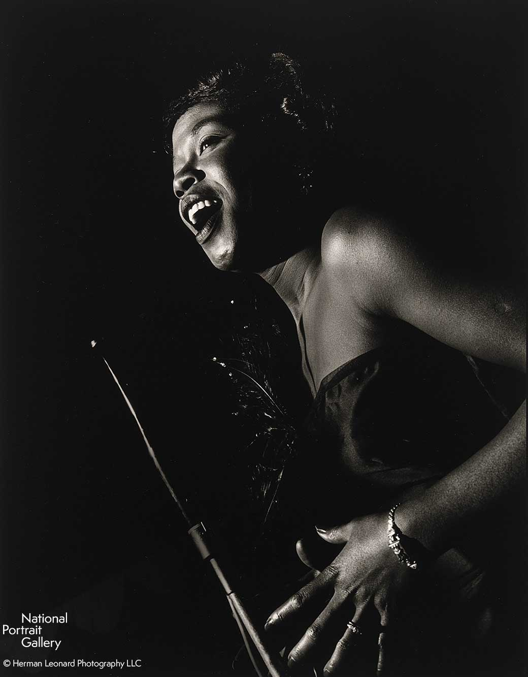 Black and white image of a woman standing in profile singing into a microphone