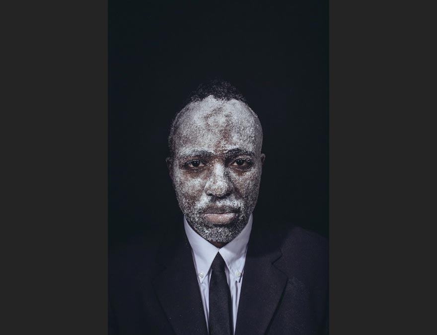 African American man in a darkened area with a white-painted face