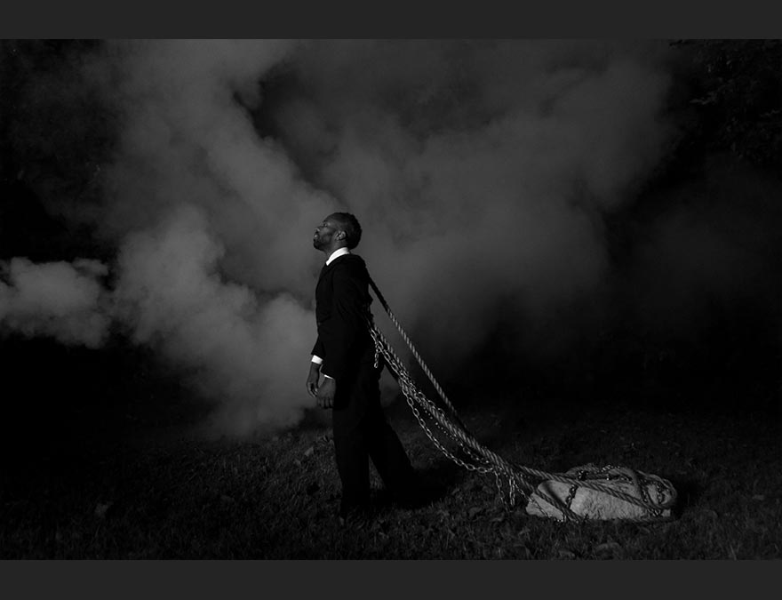 African American man in a suit dragging a large rock with ropes tied to him.