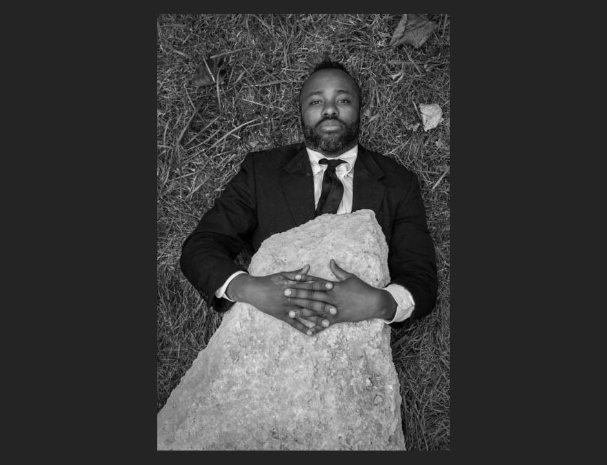 Portrait of a black man lying on the grass with a large rock covering his torso.