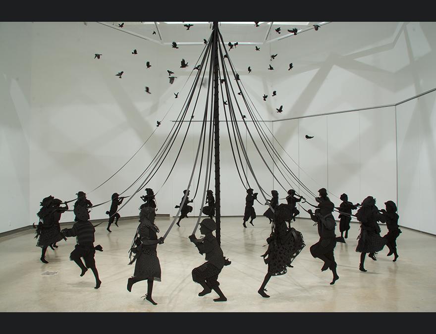 Children in silhouette dancing around a maypole