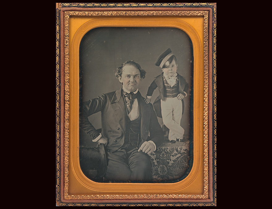 Daguerreotype of a seated man with a little person beside him