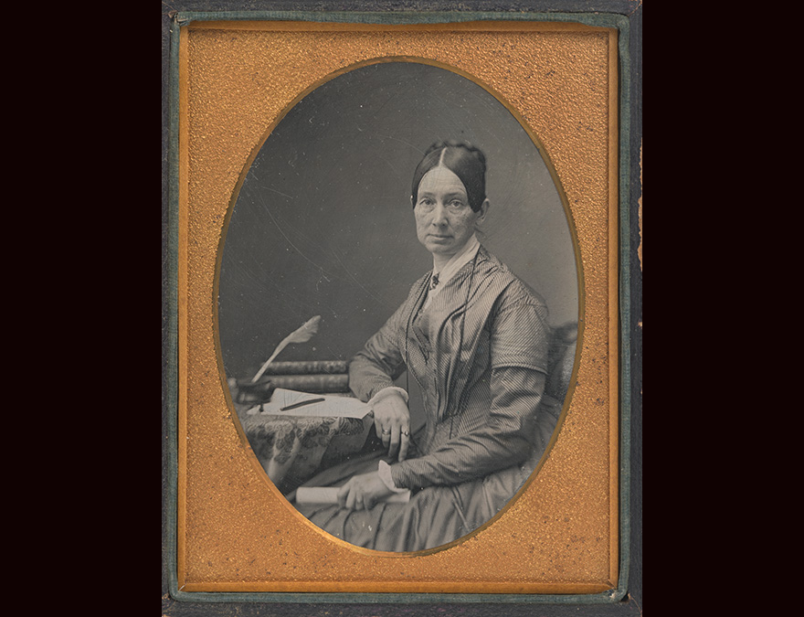daguerreotype of a 19th century woman seated at a small table