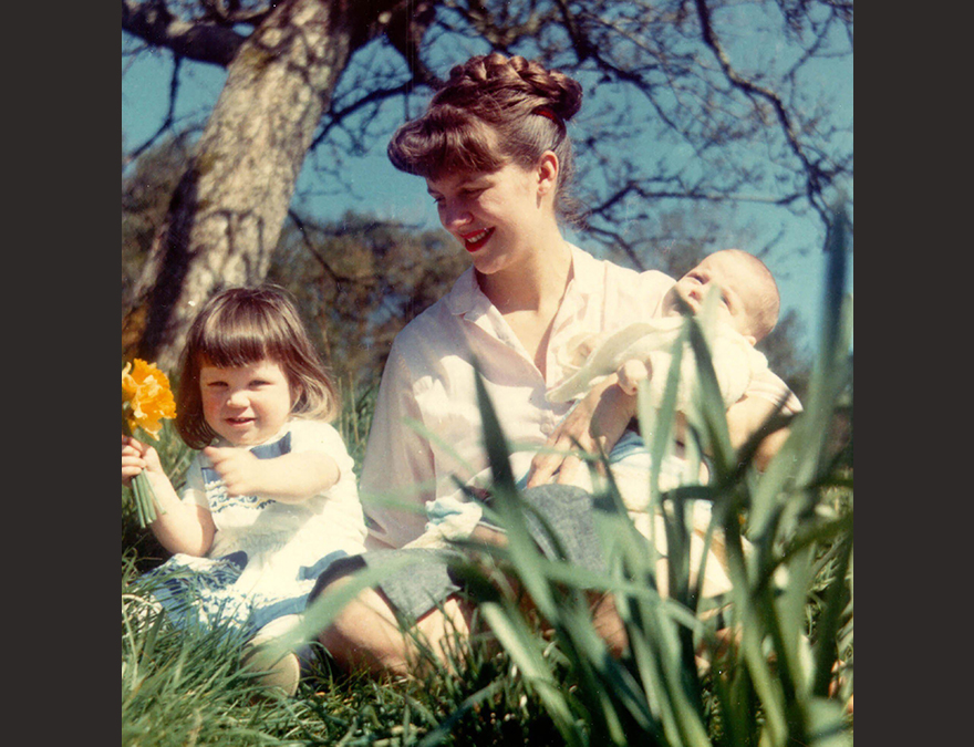 Color photo of Sylvia Plath with two toddlers, looking at flowers
