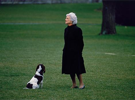 Woman in a black coat standing on a green lawn with a dog