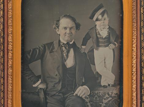 A man is seated with a little person standing beside him on a chair