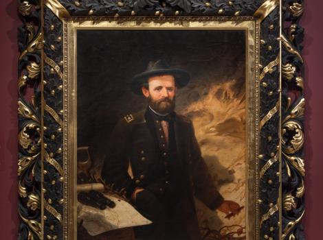 A portrait of a man in a military uniform looking at the viewer and in a beautiful black and gold frame