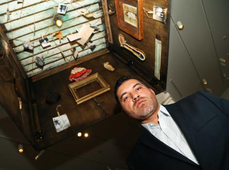 Man photographed from below. He is standing inside of a wooden box filled with photographs and other memorabilia.