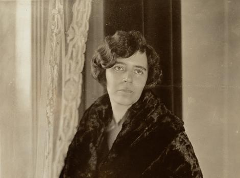 Black and white photograph of a woman in draped black clothing