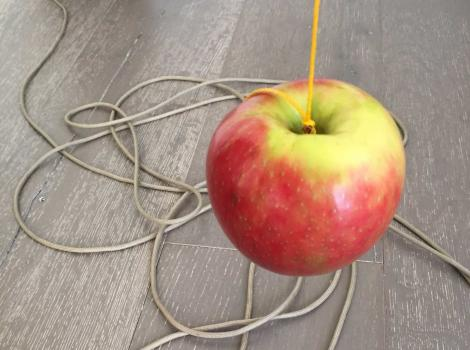 Red and yellow apple suspended by a string