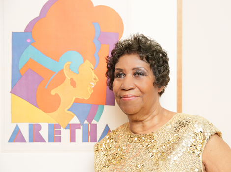 Aretha Franklin stands next to a poster of her at National Portrait Gallery