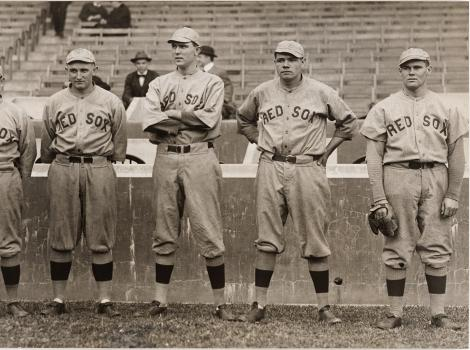 A black and white image of men wearing baseball uniforms standing in a row
