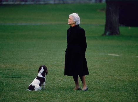 A photograph of a woman wearing a black dress and standing next to a dog outside
