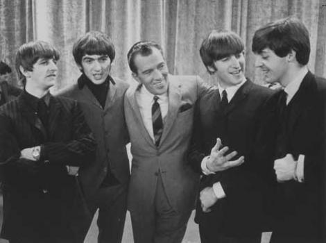The Beatles standing on stage, with Ed Sullivan in the middle