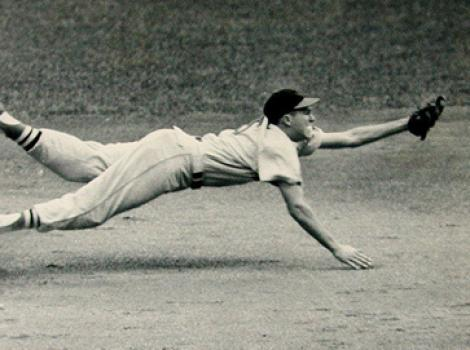 Black and white photo of Brooks Robinson diving for a ball, his body horizontal to the ground