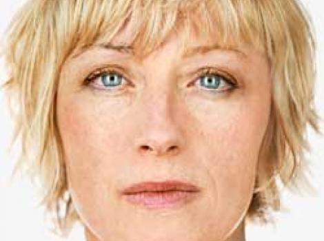 Photograph of Cindy Sherman's face, staring straight ahead into camera