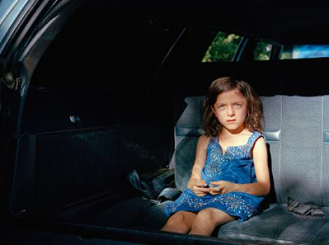 Little girl sitting in the backseat of a car
