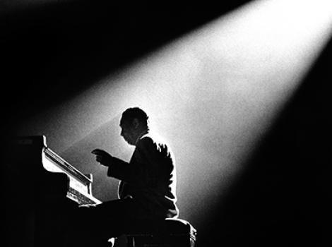 Black and white image of a man playing the piano while bathed in light