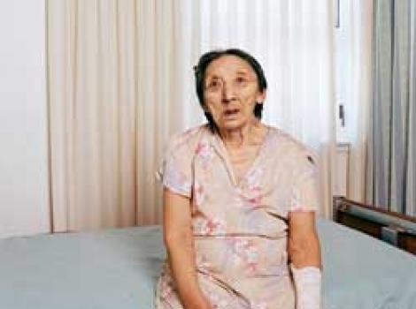 Portrait of elderly woman sitting on hospital bed