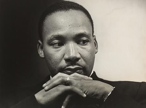 Photograph of Martin Luther King with solemn expression and hands folded underneath his face