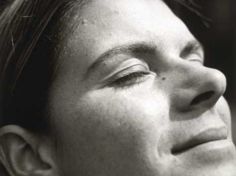Black and white photo of Mia Hamm, close-up of her face, facing upwards to sun and her eyes closed