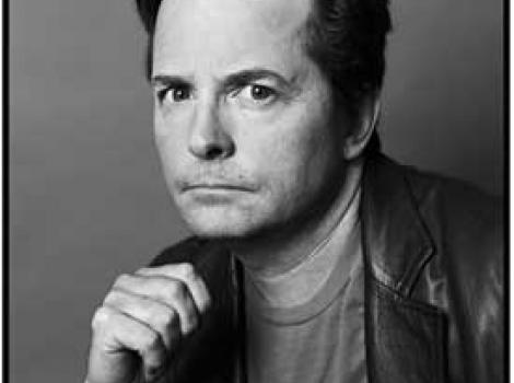 Black and white photo of Michael J. Fox with hand clutched underneath chin