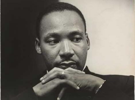 Black and white photograph portrait of Martin Lither King, with hands crossed underneath chin
