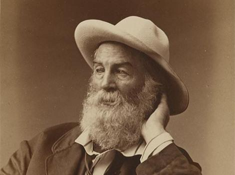 Black and white photo of Walt Whitman leaning on a desk, wearing a hat.