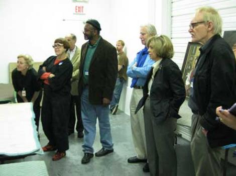 Portrait competition jurors looking at artworks
