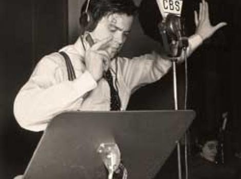 Photograph portrait of Orson Welles, speaking into microphone during a radio performance