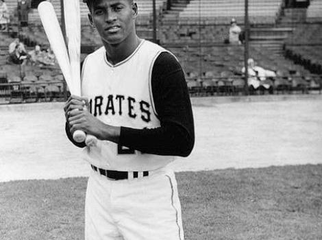 Black and white photo of Roberto Clemente in Pirates baseball uniform, holding two bats