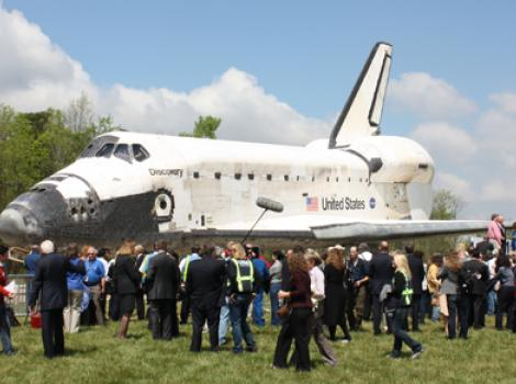 The Space Shuttle Discovery surrounded by journalists