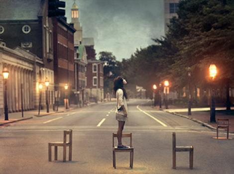 Portrait of young woman in the middle of the street, standing on chair looking upwards