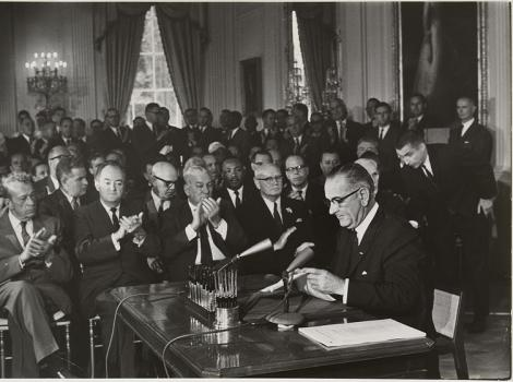 A black and white image of a man sitting at a desk signing a piece of paper with a lot of men clapping behind him
