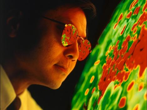 A man wearing light-protecting glasses looking at a projection of a large green and red mass